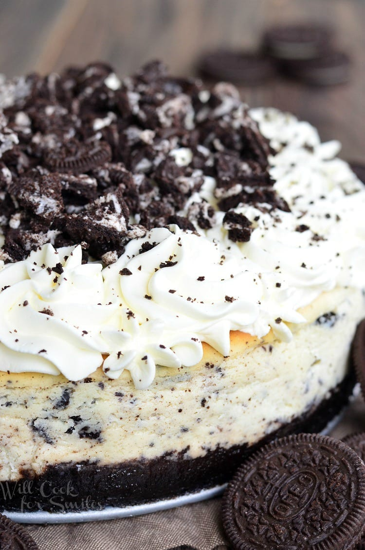 Oreo cheesecake on a table with oreo cookies to the right