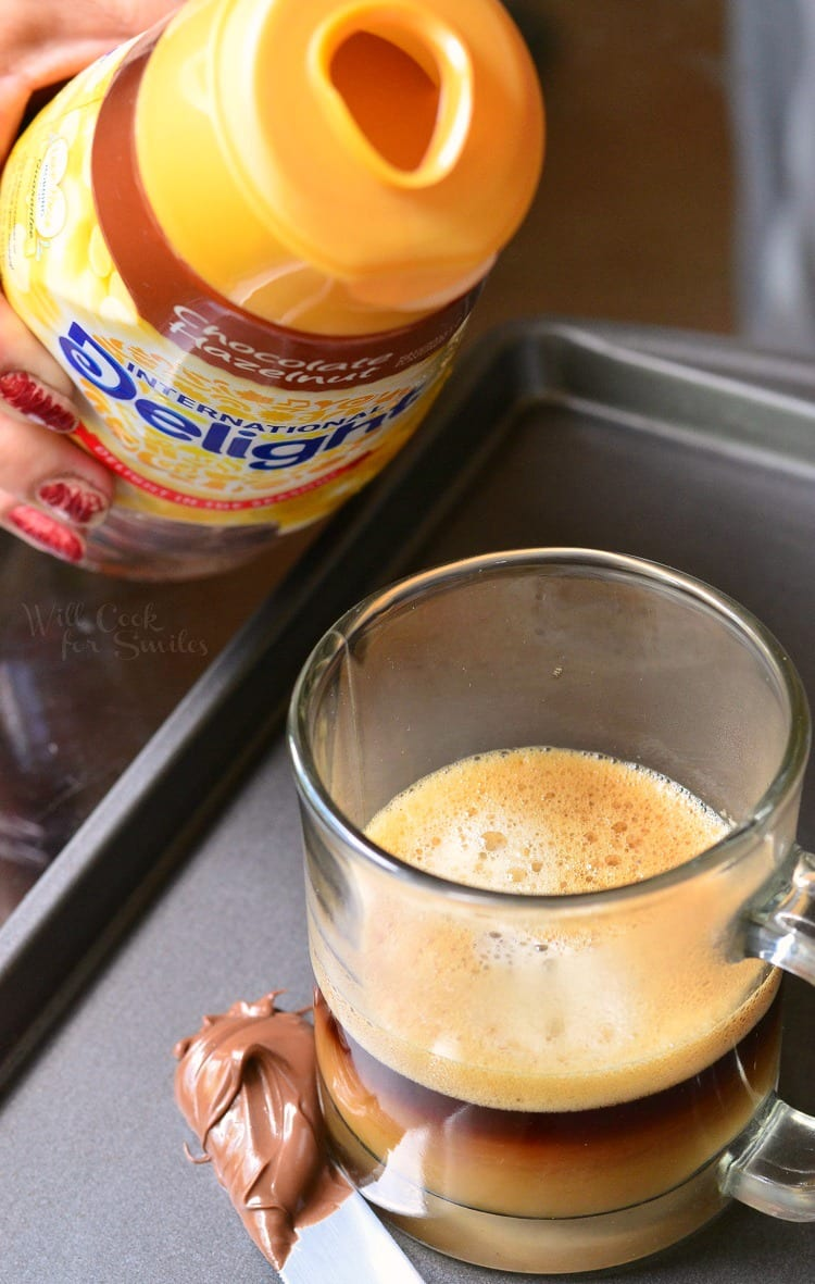 pouring chocolate hazelnut creamer into clear glass mug that is on a baking sheet with a knife to the left with chocolate on it