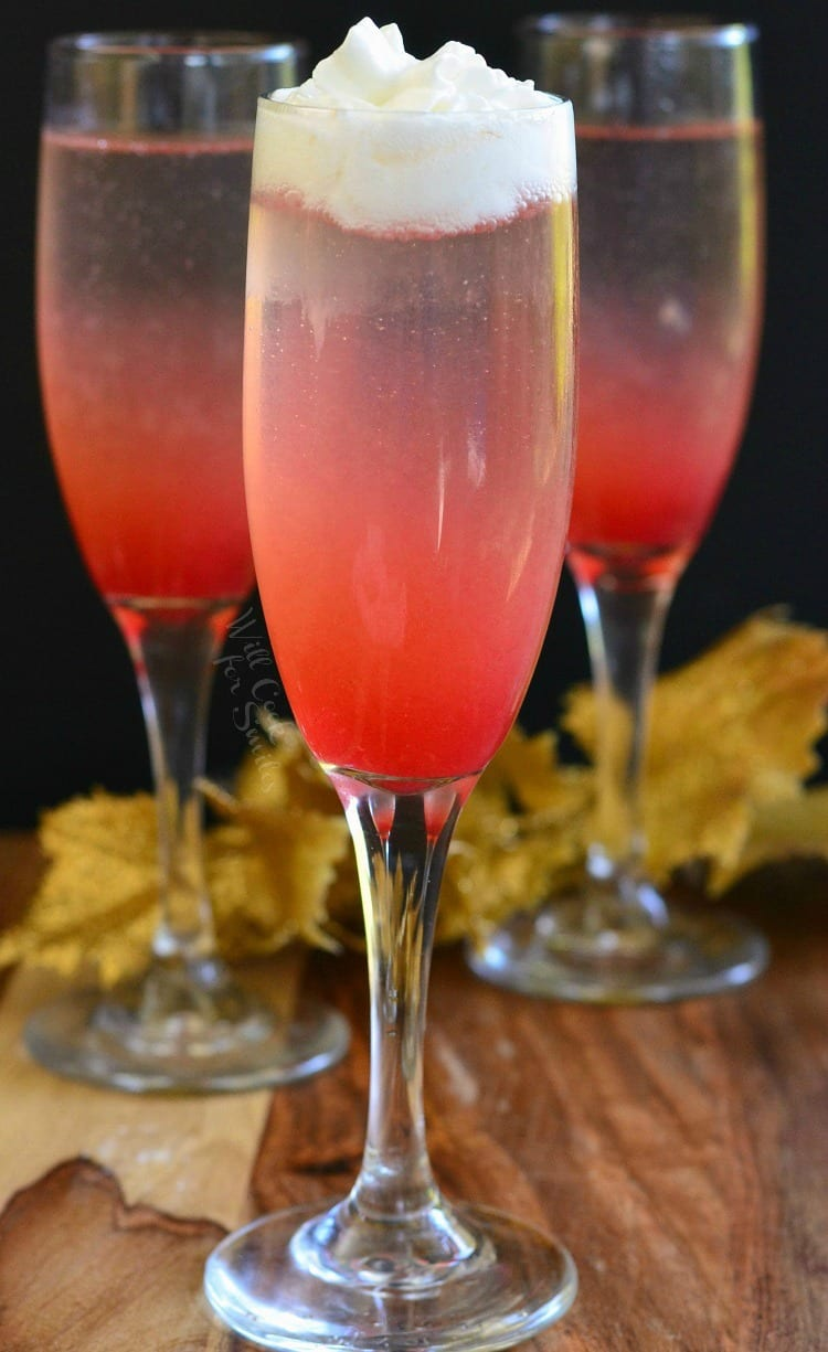 3 Raspberry Italian Soda Champagne Cocktail in a champagne flute on a table