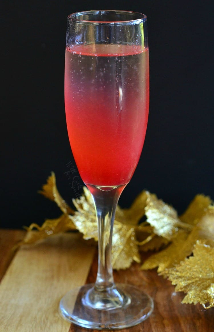 Raspberry Italian Soda Champagne Cocktail in a champagne flute on a table