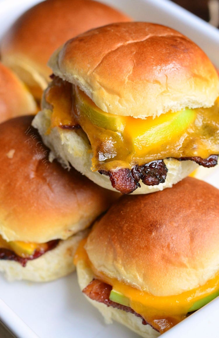 Apple Bacon Cheddar Baked Sliders stacked on top of each other in a white baking dish