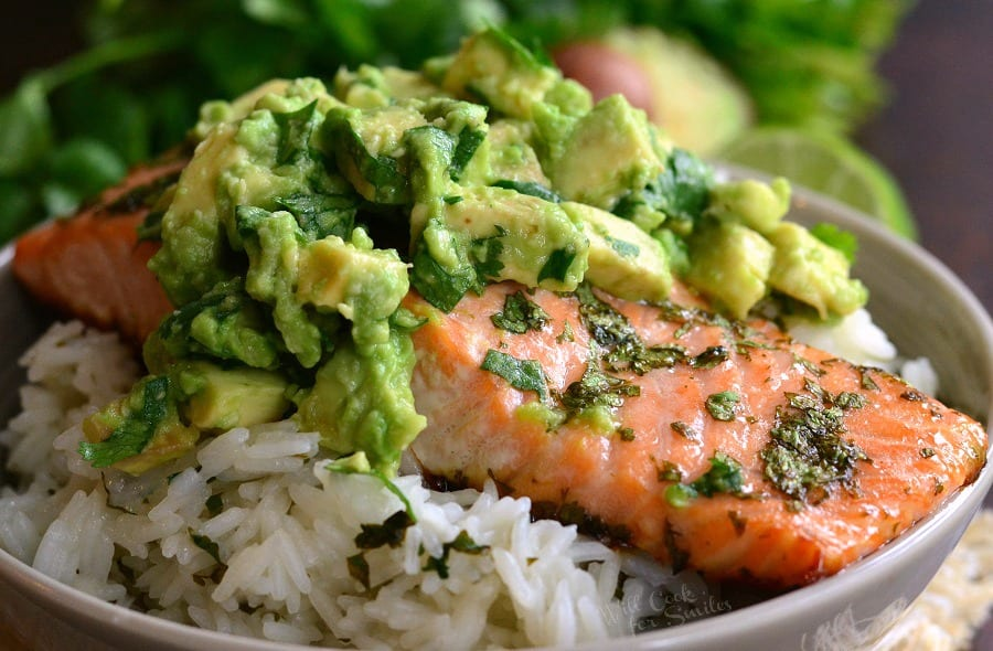 horizontal view of Salmon over Rice with avocado on top in a bowl