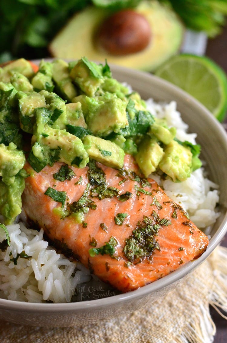 salmon topped with avocado over rice in a bowl on a table with avocado in the background