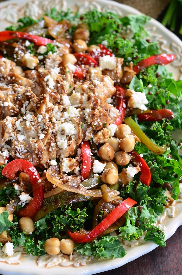 Top view of photo of kale salad topped with chicken and veggies that have been sauteed in balsamic on a white plate with dressing, chick peas, and finally, lots of feta cheese.