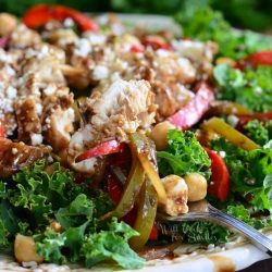 White decorative bowl filled with balsamic chicken, veggies and chick pea salad as viewed close up.