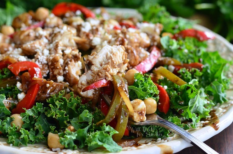 horizonal kale salad topped with chicken and veggies that have been sauteed in balsamic on a white plate with a fork dressing, chick peas on a plate with a fork
