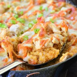 Black skillet filled with creamy siracha chicken and quinoa bake on a wooden table