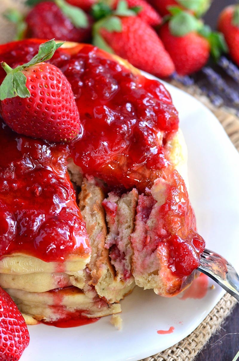 Strawberry Lavender Pancakes with strawberries and strawberries syrup on top on a white plate with a fork