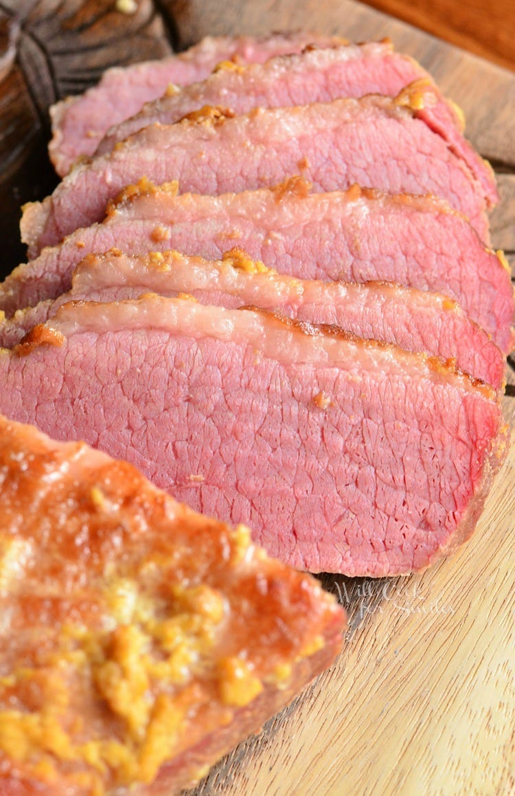 top view Oven Baked Corned Beef Brisket half of it slices on a wood cutting board