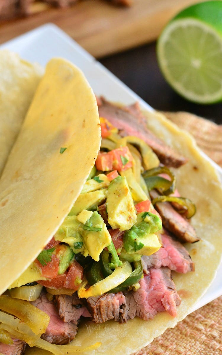 Carne Asada Tacos. Juicy flank steak marinated and seared to perfection, it's topped with onions and poblano peppers sauteed in steak marinade and fresh tomato avocado topping.