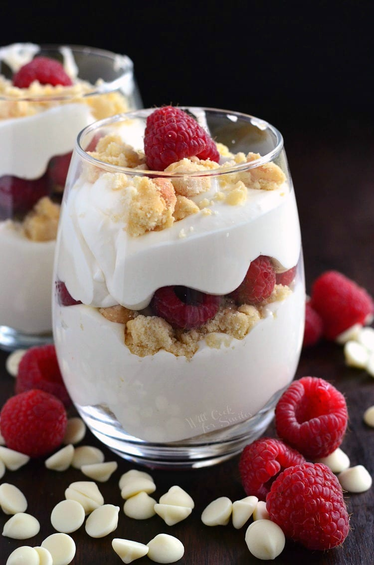 Easy Raspberry White Chocolate Mousse Parfait in a glass on a table with white chocolate chips and raspberries