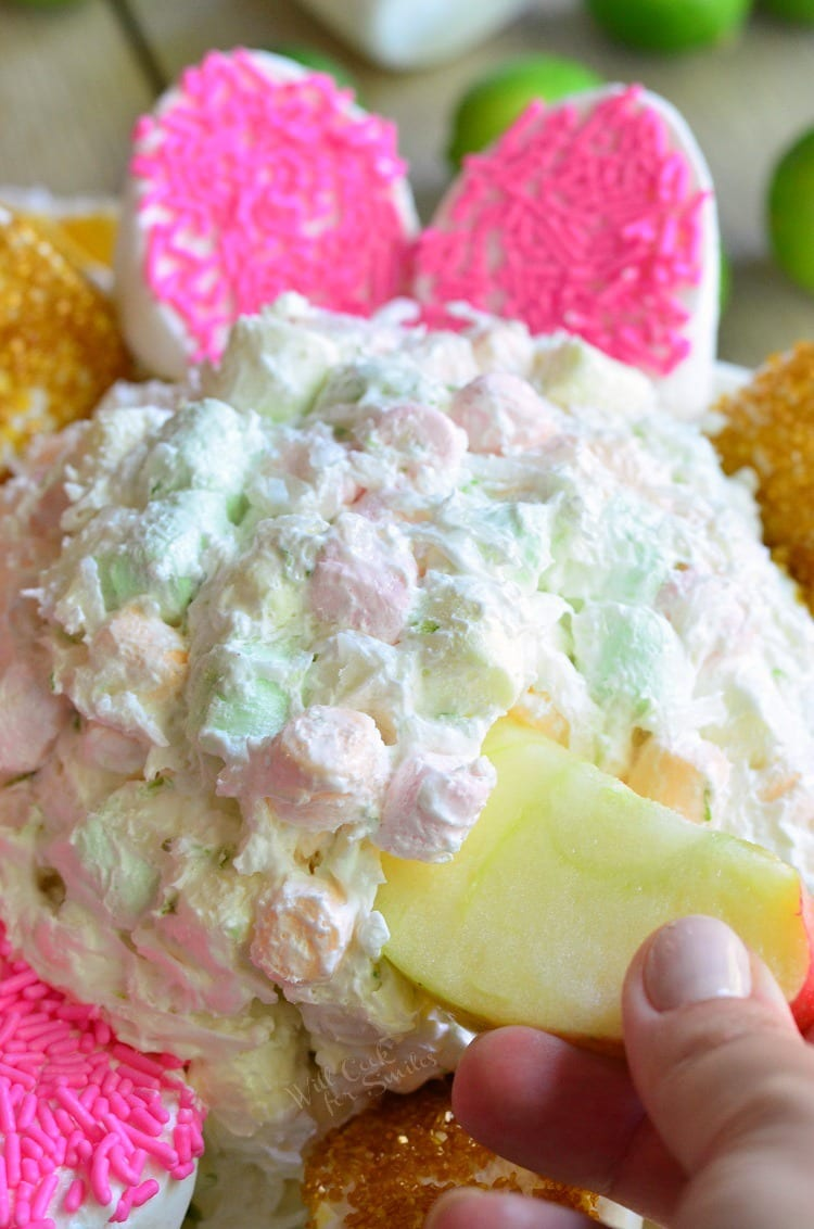 dipping apples into Coconut Key Lime Marshmallow Dip