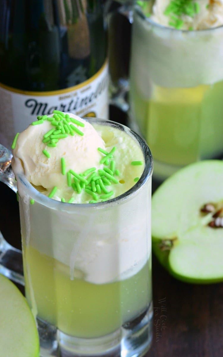 Green Apple Ice Cream Soda Float in a glass mug with Martinelli's Sparkling Apple Cider in the background a sliced apples on a table