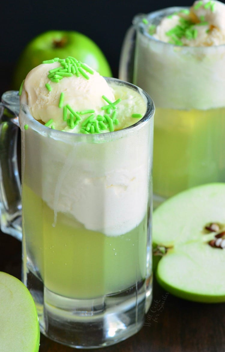 Green Apple Ice Cream Soda Float in a glass mug with green sprinkles on top with apples around the tables
