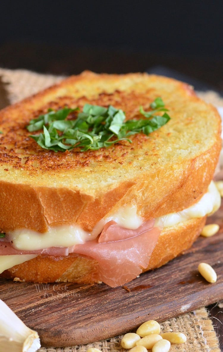 Italian Garlic Bread Grilled Cheese with parsley on top as garnish on a cutting board with pine nuts around