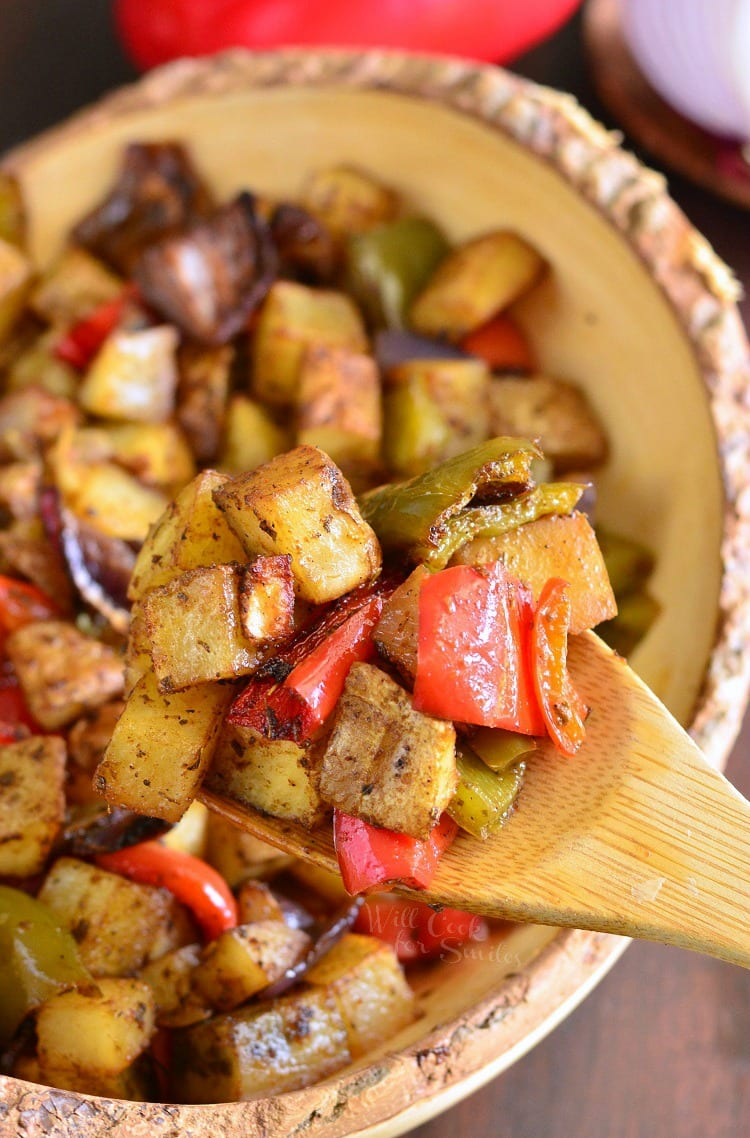 Southwest Roasted Potatoes in a yellow bowl with a wooden spoon scooping some out