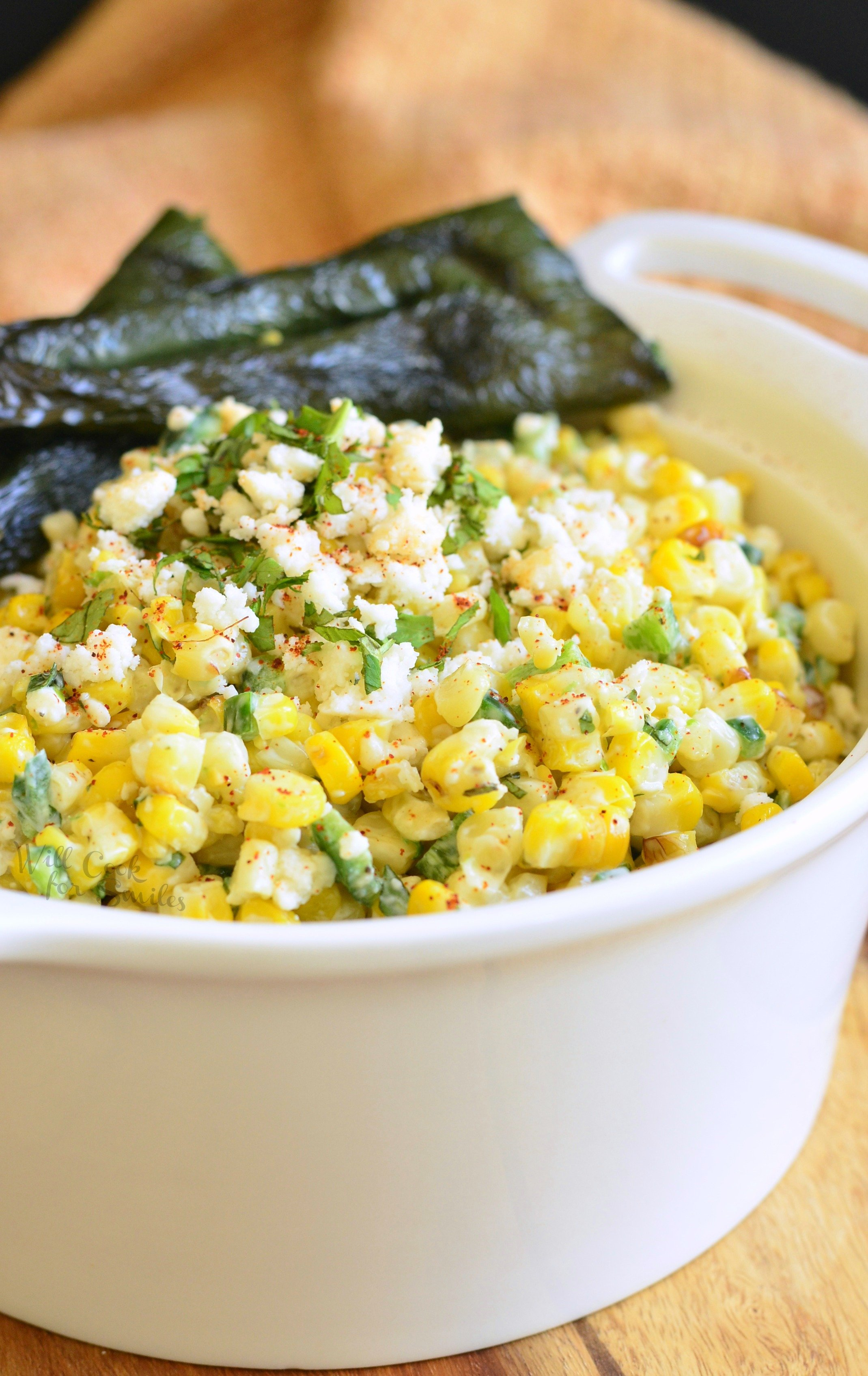 corn salad topped with crumbled cheese with some grilled poblano peppers in a bowl