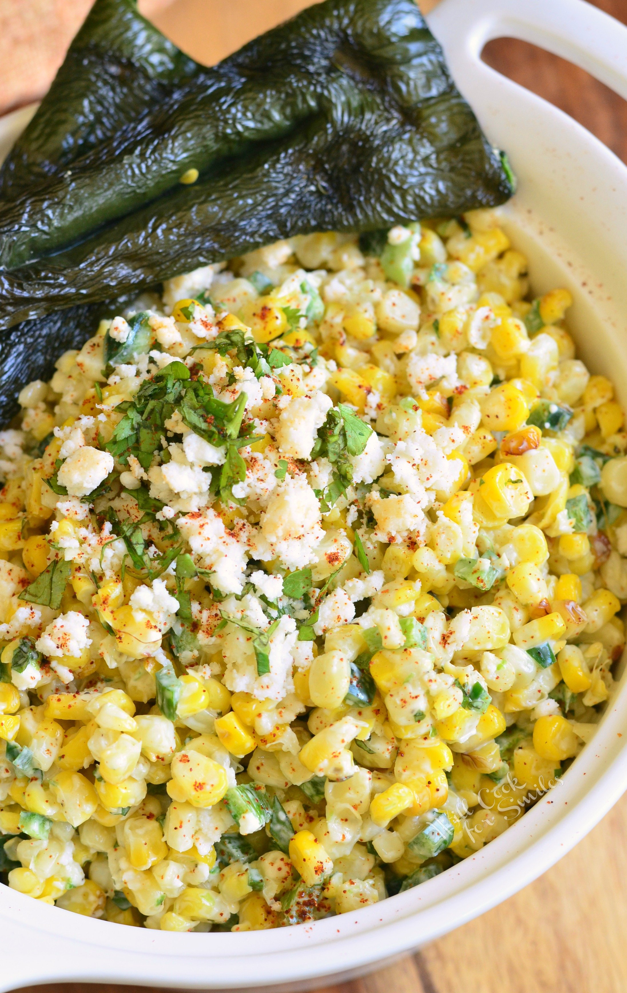top view of corn salad with white crumbled cheese on top and grilled poblano peppers on the side
