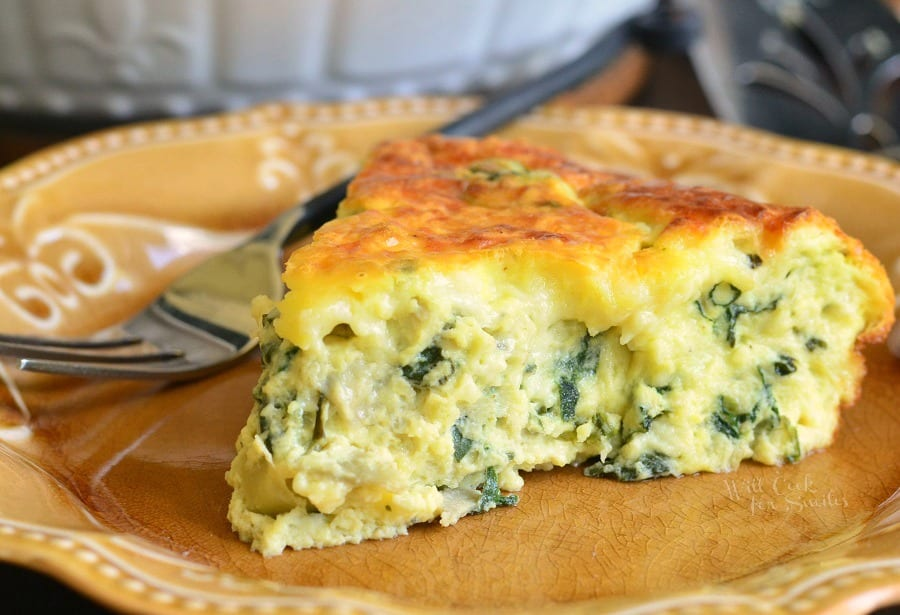 spice of spinach quiche on a brown place with a fork