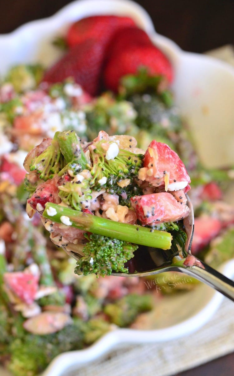 Strawberry Asparagus Broccoli Salad being scooped out of white bowl with a spoon