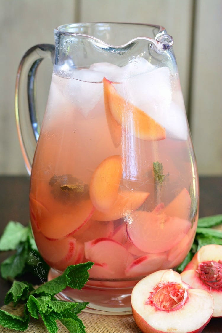 Mint Peach Rose Spritzer in a glass pitcher on a table with mint and cut peaches