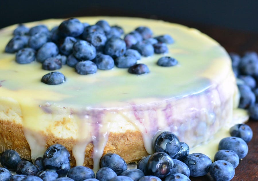 White Chocolate Blueberry Cheesecake with blueberries on top on a table with blue berries around it