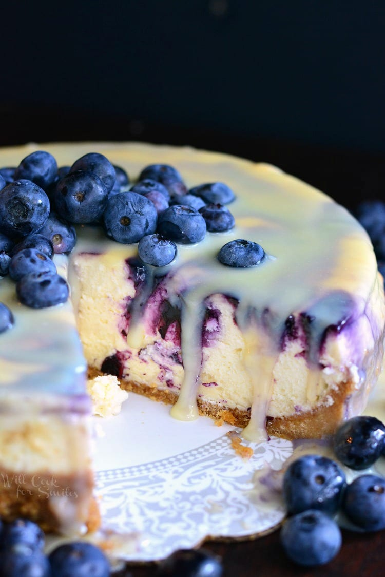 White Chocolate Blueberry Cheesecake with a slice missing on a plate