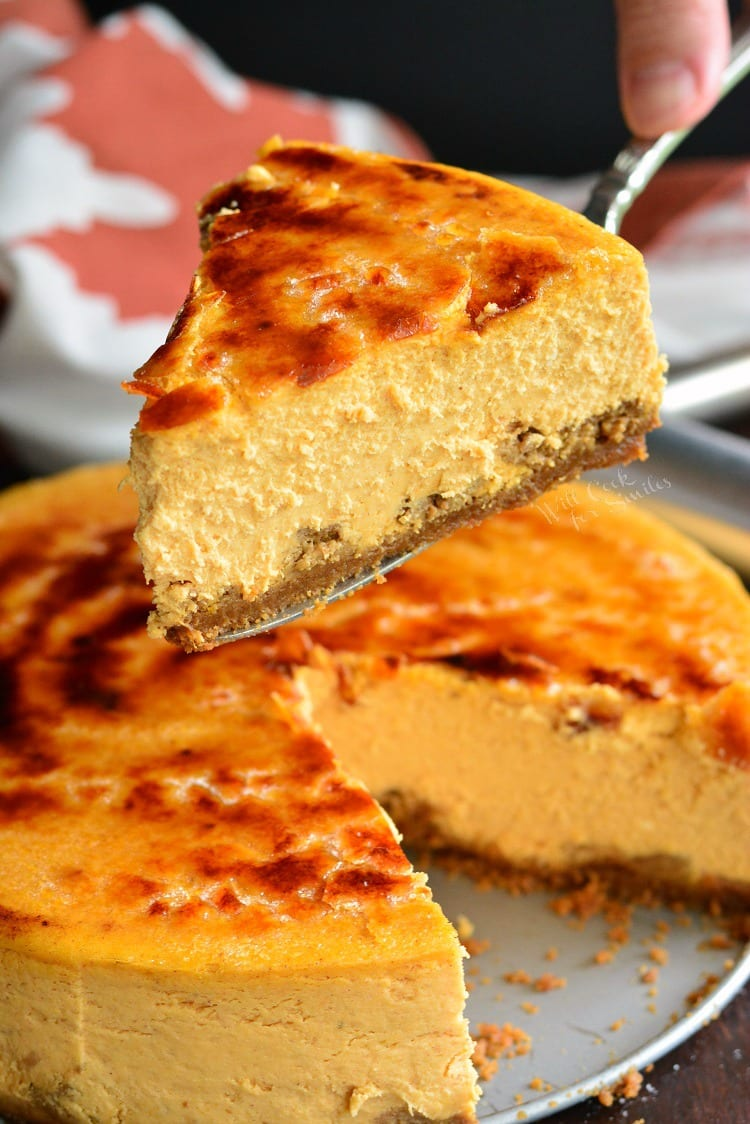 lefting a piece of Creme Brulee Pumpkin Cheesecake up with a pie spatula with the rest of the cheesecake below it