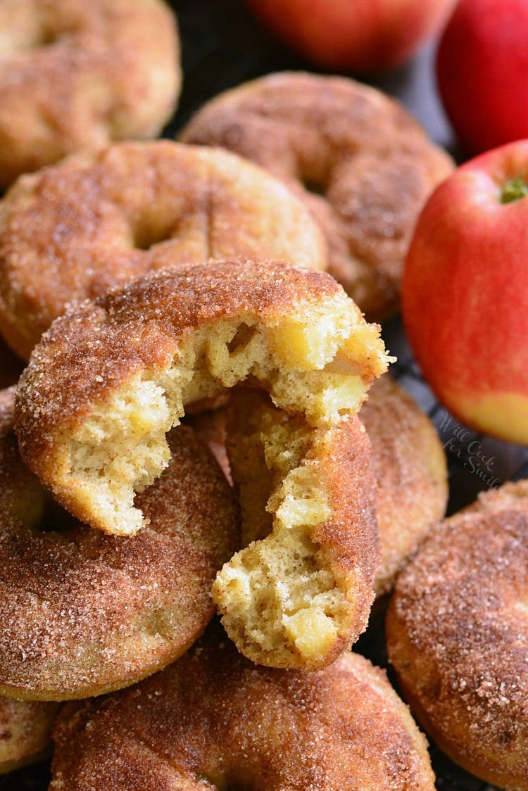 Apple Pie Baked Doughnuts one cut in half on a cooling rack with apples in the background