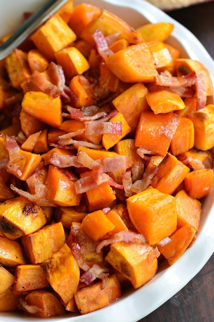 Maple Bacon Roasted Sweet Potatoes in a serving bowl on a wood table