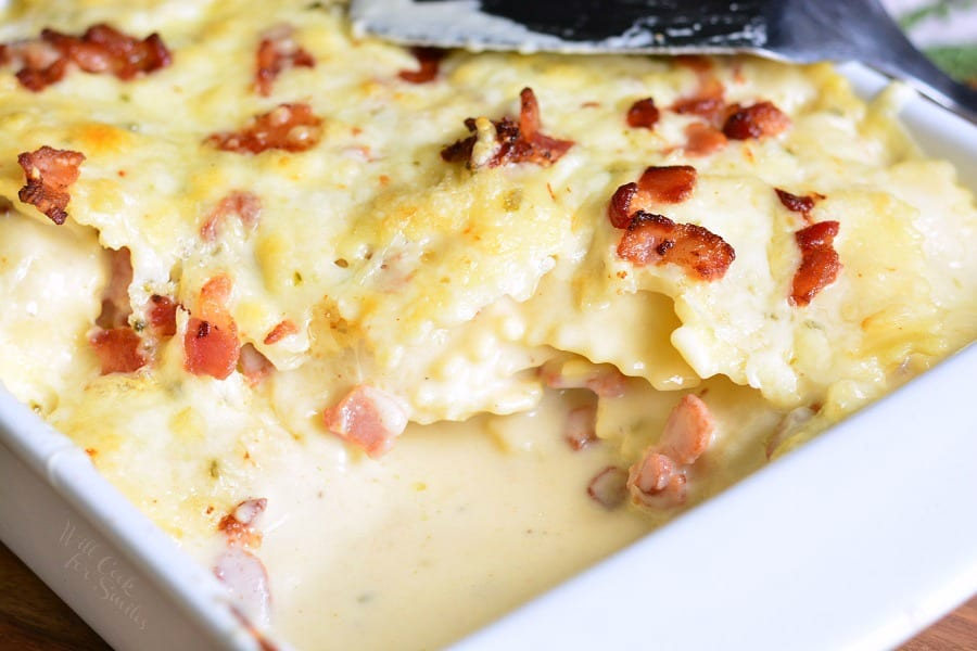 Baked Ravioli Mac and Cheese with Bacon in a white casserole dish with a spatula on top