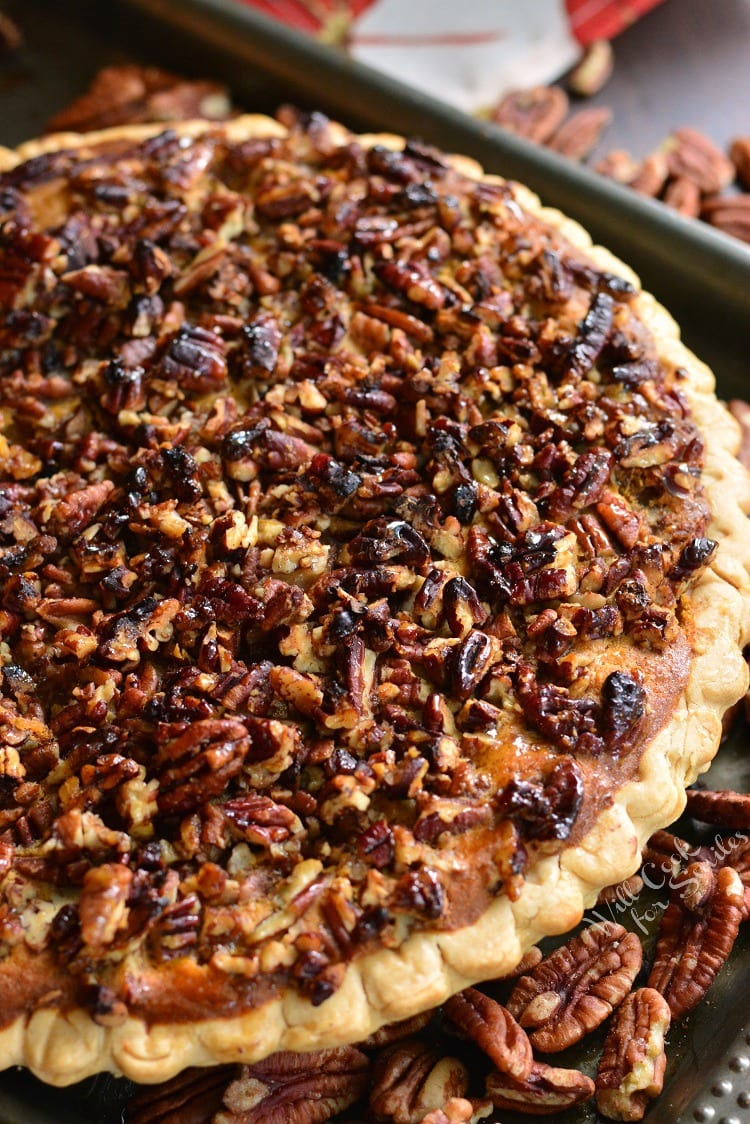 Pecan Crunch Sweet Potato Pie on a baking sheet with pecans all around it