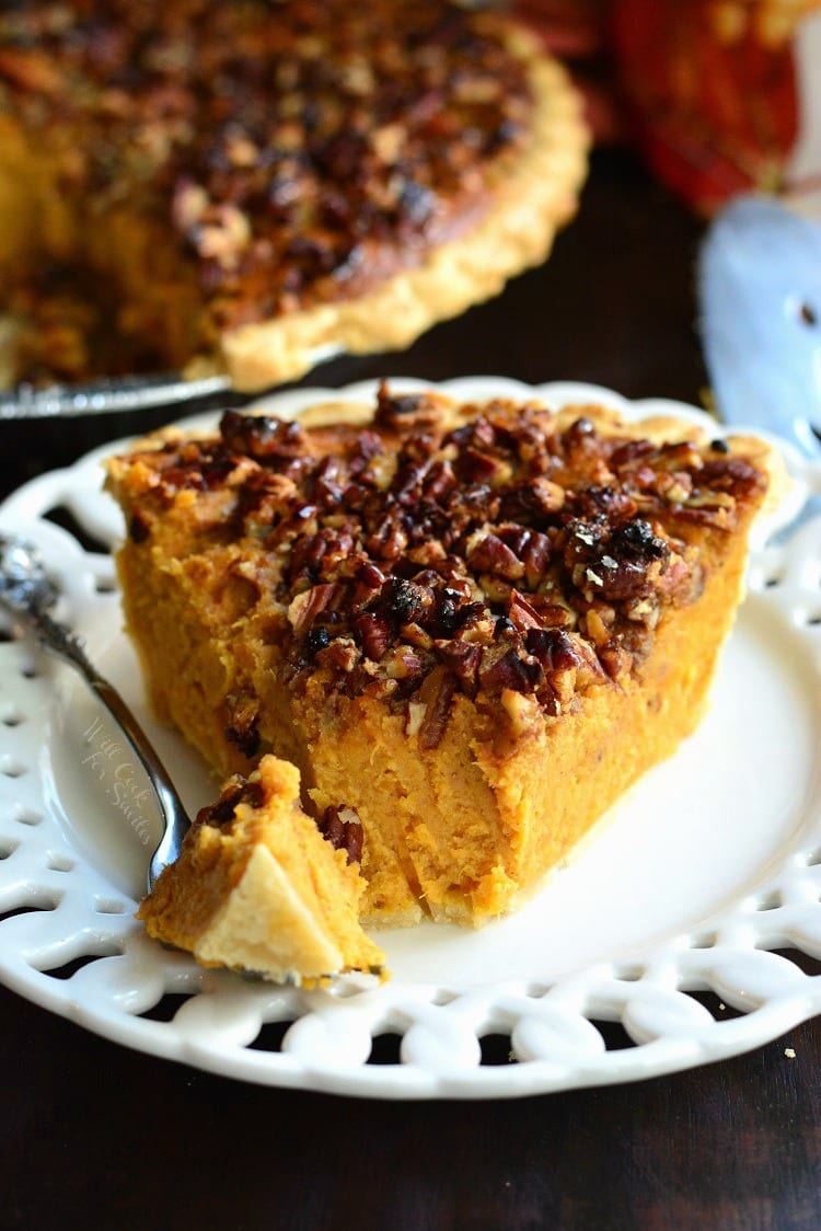 Pecan Crunch Sweet Potato Pie on a plate with a for with a bite on it the rest of the pie in the background