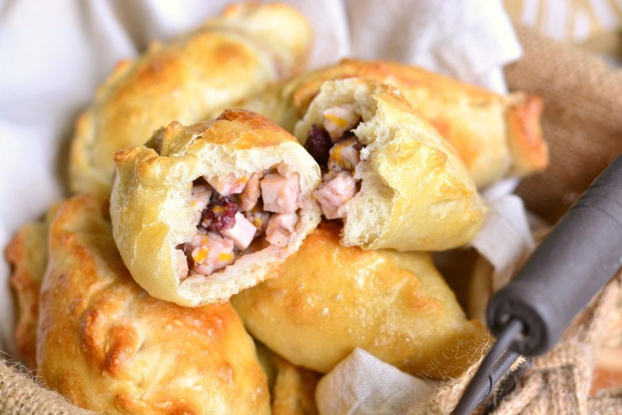 Turkey Cranberry Baked Piroshki cut in half in a basket with a dish cloth in the bottom