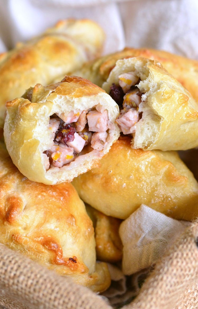 Turkey Cranberry Baked Piroshki cut in 2 in basket with a dish cloth in the bottom