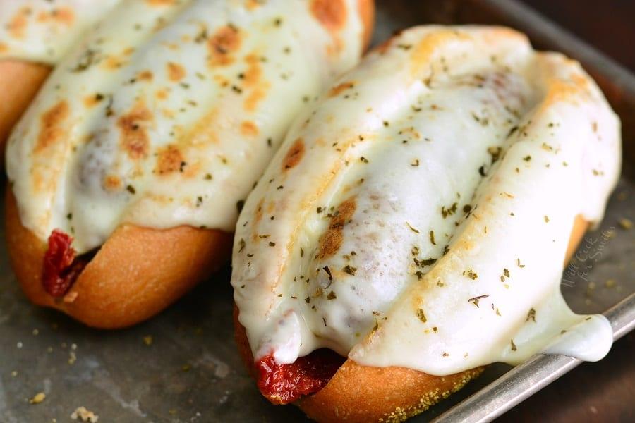 Tomato Mozzarella Italian Sausage Hoagies on a baking sheet