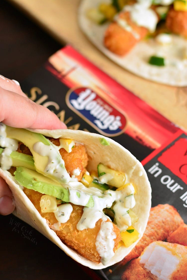 Crispy Fish Tacos with Cucumber Mango Relish. These tacos are made with crispy fish fingers, sweet and spicy cucumber mango relish, fresh avocado, and topped with avocado cilantro crema. #fishtacos #crispyfish #cod #fishsticks #tacos #mangorelish