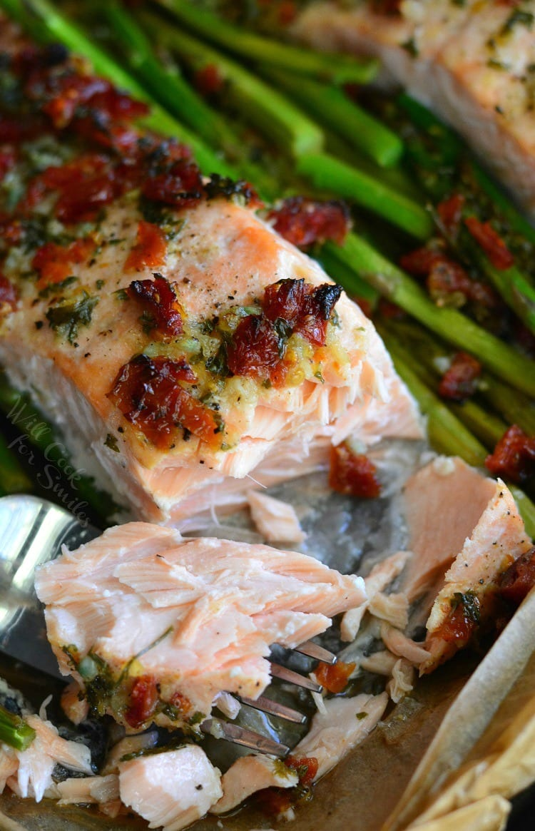 Sun Dried Tomato Lemon Baked Salmon and Asparagus in parchment paper on a baking sheet