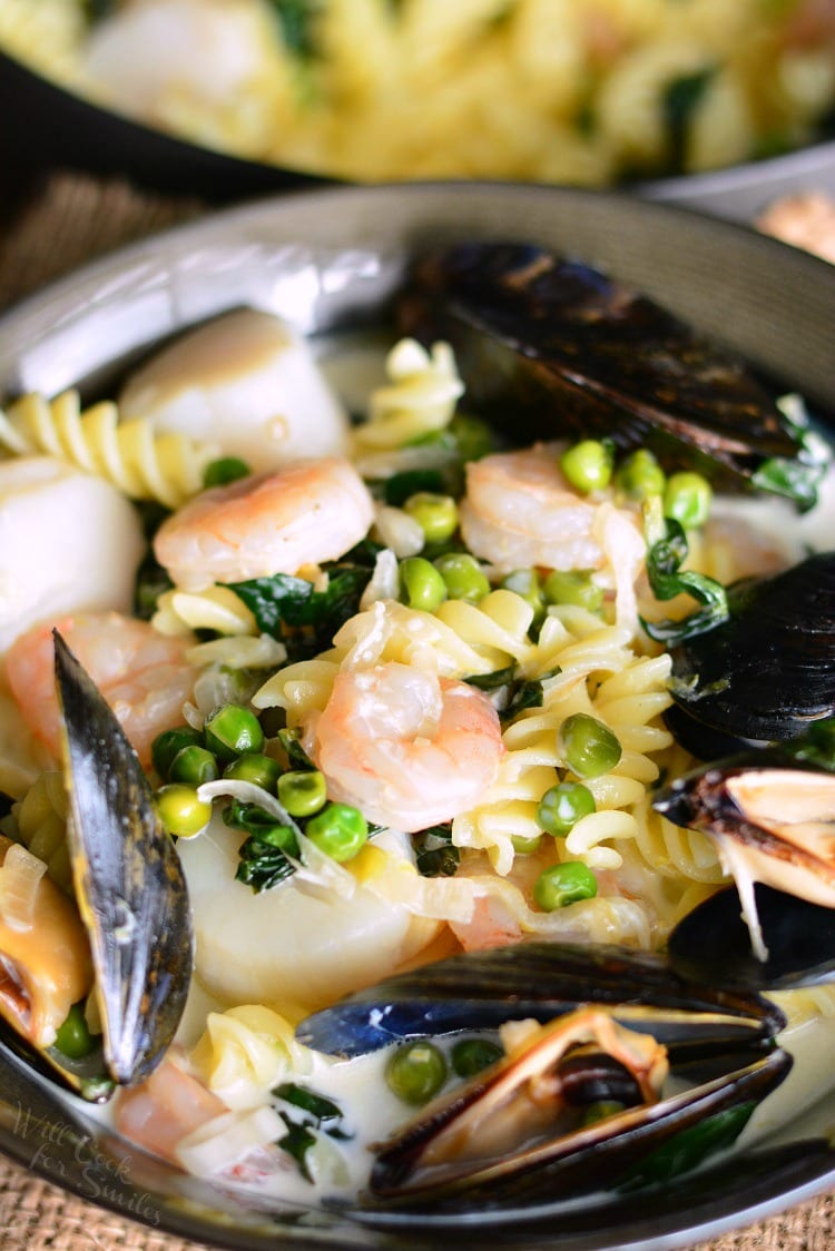 Creamy Spinach and Peas Seafood Pasta. Tasty and easy seafood pasta dish loaded with different kinds of seafood, spinach, peas, and a creamy white wine lemon basil sauce. #pasta #seafood #creamsauce #shrimp #spinach