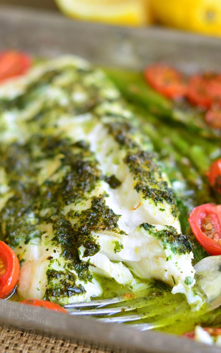 Lemon Herb Butter Cod with Asparagus and Tomatoes in a baking dish with a fork