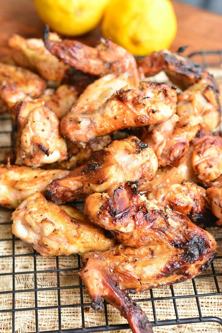 Grilled Chicken Wings stacked up on a cooling rack with lemons in the background