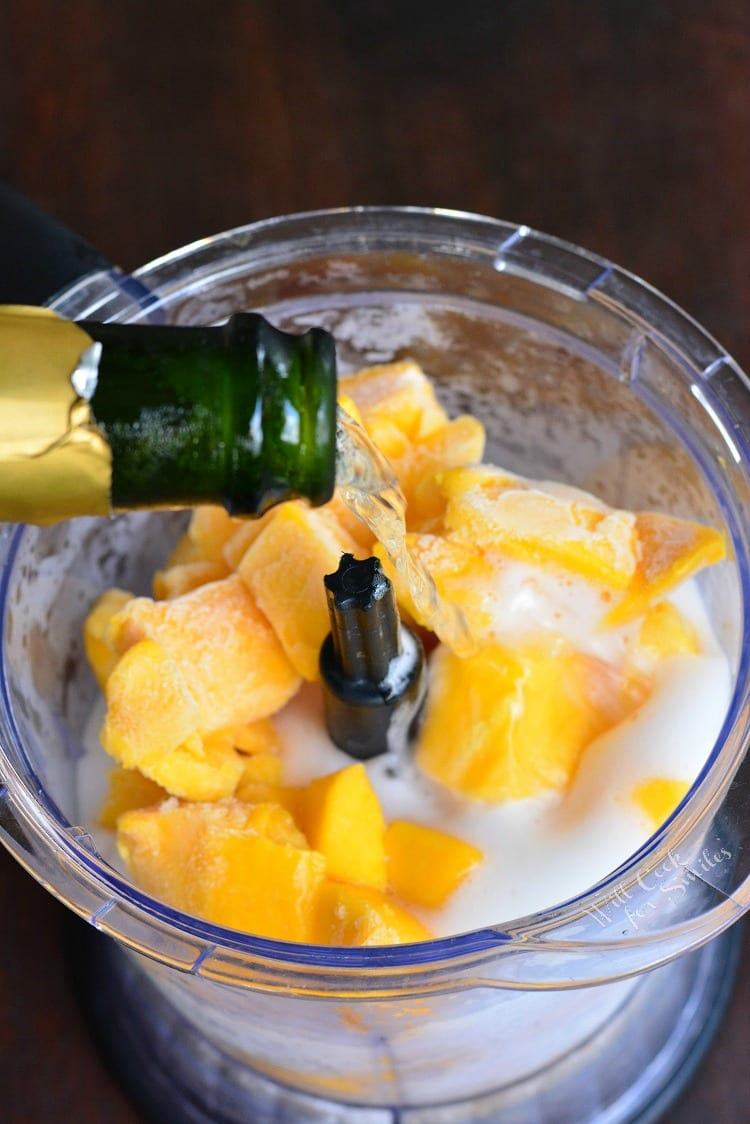 pouring Champagne into food processor with frozen mango