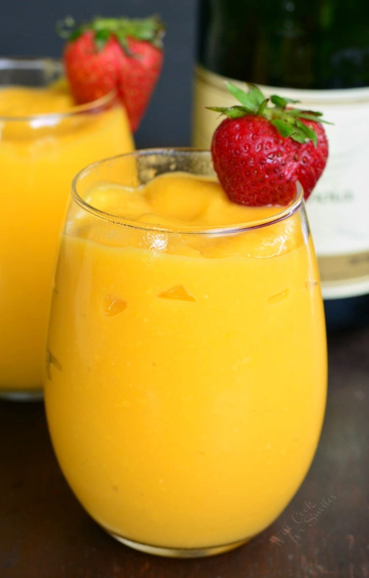3-Ingredient Mango Champagne Slushies in a stemless wine glass on a table with a strawberry garnish