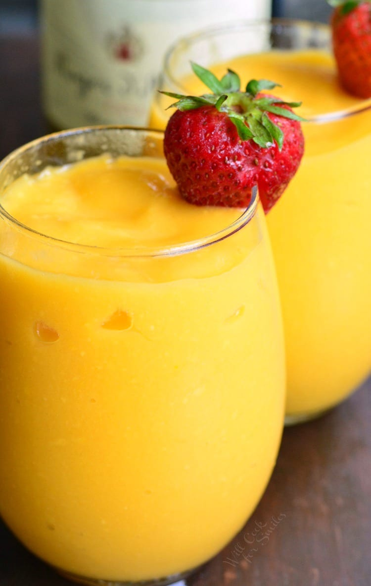 3-Ingredient Mango Champagne Slushies in a stemless wine glass with a strawberry as garnish