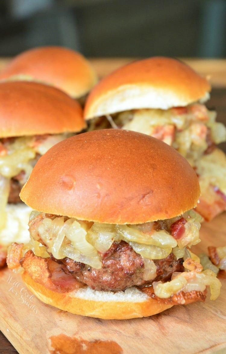 Bacon Burger Sliders with Bacon Caramelized Onions on a bun sitting on a cutting board