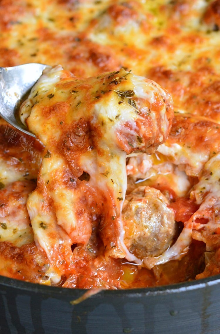 Cheesy Meatball Dip recipe in a pan with a meatball being lifted with by a fork