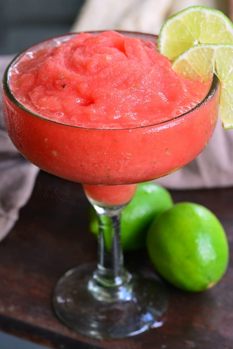 Watermelon Lime Frozen Margaritas in a glass with lemon as garnish sitting on a wood cutting board with lemons