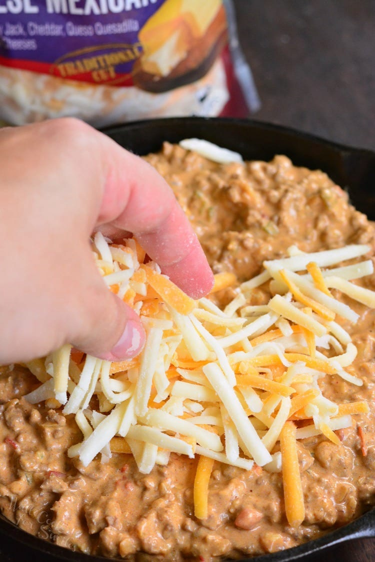 Creamy Beef Taco Dip in a pan sprinkling cheese over top.