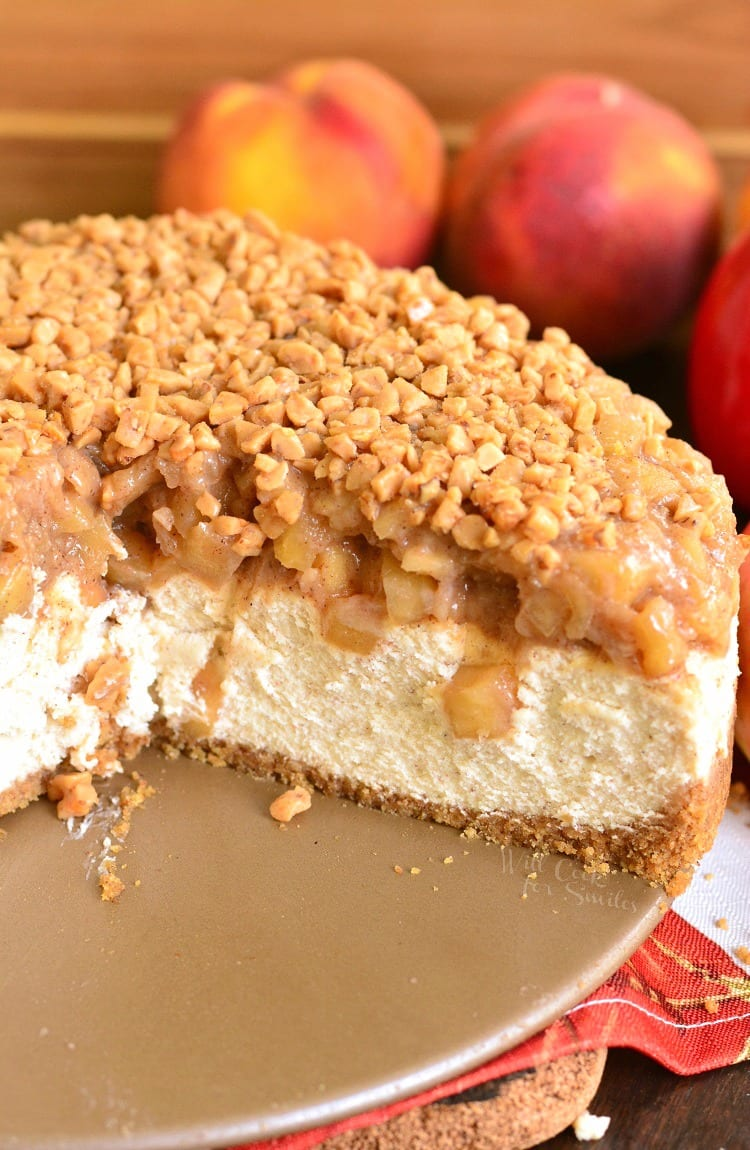 Apple Pie Cheesecake with apples on a cutting board