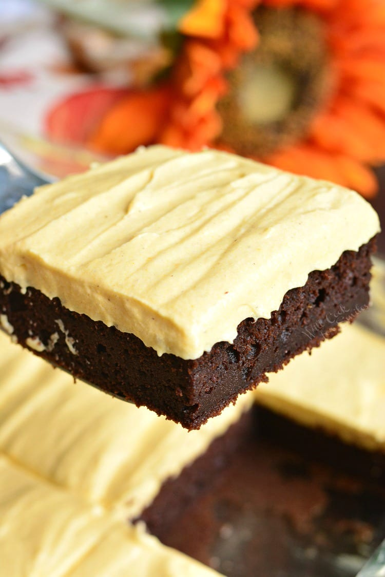 Frosted Pumpkin Brownies being lifted out pan
